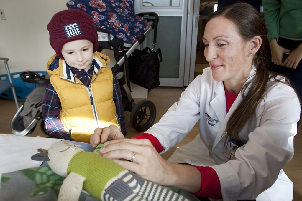 kids watches an ER doctor exam his bear's arm.