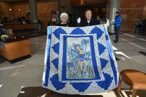 couple holds up a quilt