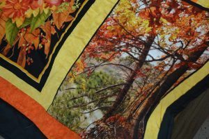 a quilt panel that shows trees and fall colors
