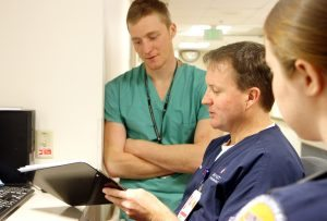 PVH Medical Unit RN Jimi Killen is shown in this photo discussing his job with shadowing first-year resident Austin Fain and UNC nursing student Julia Knox.
