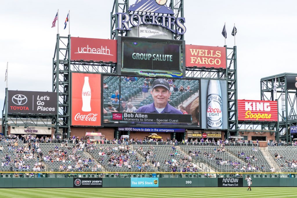 Stands at a Colorado Rockies game, a symbol of me appreciating our American way of life.