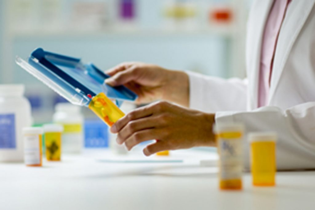 A pharmacist measures medication into a bottle.
