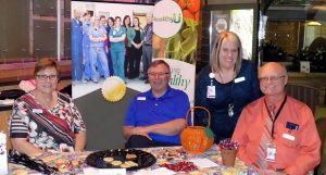 Four people are pictured at an event during a Patient Centered Care Awareness month activity.