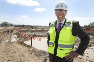 A man in a construction helmet stands near a dirt pile where UCHealth Longs Peak Hospital will be.