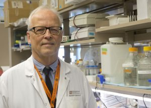 Dr. Eric Poeshcla, chief of Immunology at the University of Colorado School of Medicine, poses in his lab. He's wearing a white coat.