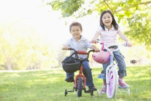 Two young kids riding a bike