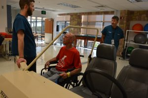Patrick Buxton, a patient in the Rehabilitation Patient Care Unit at Memorial Hospital Central, works with Andrew Bettlach, an occupational therapist, to practice transferring from a wheelchair into a simulated car. Gregory Braeger, therapy manager, looks on.