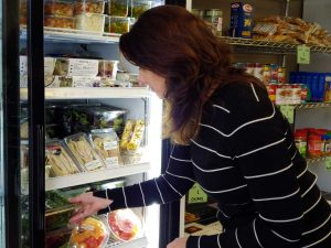 women puts cold food inside a refrigerator at a food pantry in Fort Collins