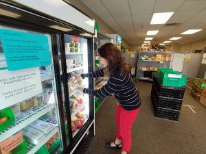 women stalks food in a food pantry in Fort Collins