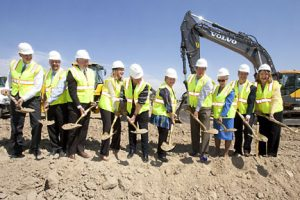 A photo of 10 people as they prepare to dig up the first shovels of dirt, breaking ground on UCHealth Greeley Hospital.