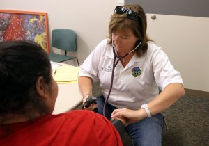 Julie Bower, paramedic for UCHealth EMS, takes the blood pressure of a women who was complaining of chest pains during EMS' weekly clinic at the Larimer County Community Corrections