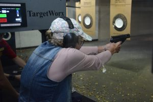 A woman practices marksmanship at a shooting range.