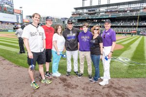 Volunteer Bob Allen and his family are shown on the field at Coors Field before a Colorado Rockies baseball game.