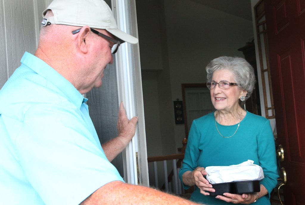 Meals on Wheels Fort Collins volunteer Larry Kerr is shown delivery a meal to client Shirley Penner at her home.