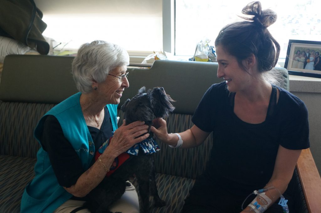 Marta, a therapy dog at University of Colorado Hospital, and her owner, Louella Stoever, visit with patient Kate Buffington.