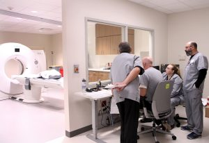 A team of imaging experts at UCHealth Longs Peak Hospital practice using a new CT machine during a training. You see the workers in one room and the large white CT machine in an adjacent room.