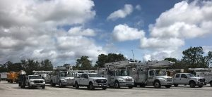 A fleet of white SUVs wait on a highway to get the go-ahead to drive on flooded highways to Miami after Hurricane Irma. Blue skies show above the SUVs, a sign that the storm has passed.