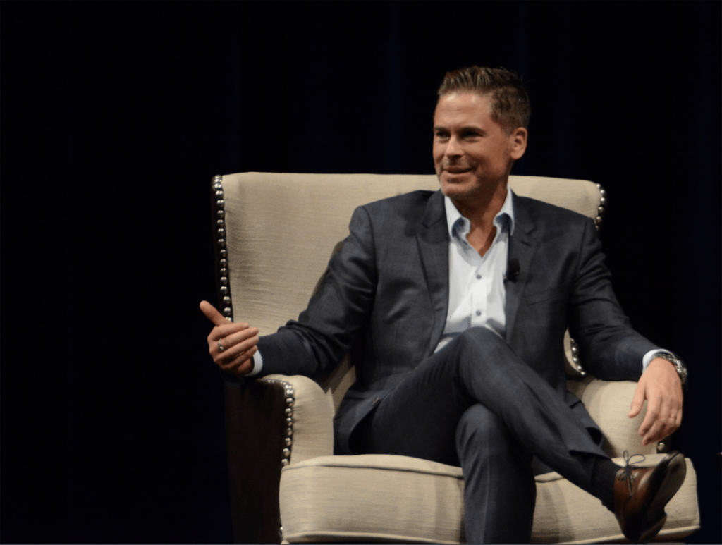Actor Rob Lowe sits in a chair and speaks during an event to benefit CeDAR, a drug rehabilitation center.