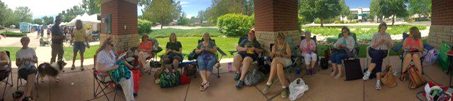 A group of people sit in lawn chairs at Fort Collins Farmers Market knitting.