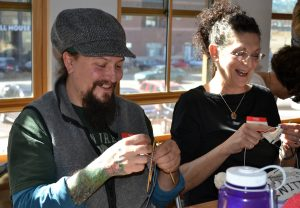 "Dustin ""Nature"" Duvall of Fort Collins and Diane Volpe of Loveland share a laugh as they create knitted knockers."