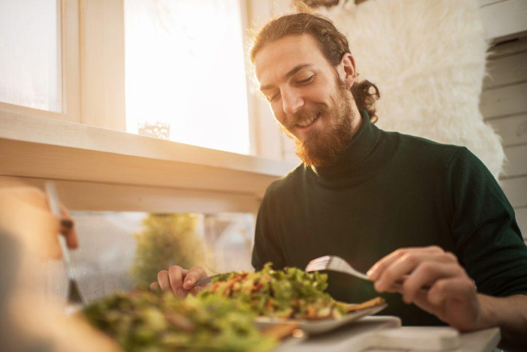 man sits at a table eating a salad.