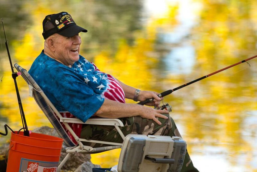 J.D. Hill sitting in a chair fishing by a lake with a tie-dye american flag shirt