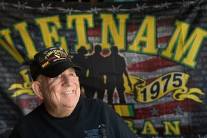 J.D. Hill at his home with a Vietnam Veteran flag behind him.