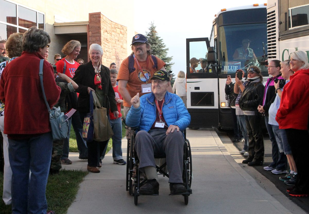 WWII Pfc. Jim Ingram, pushed by Sgt. John Darcy, gives the crowd a thumbs up as he gets ready to load the bus for the Honor Flight Northern Colorado trip on Sept. 17-18, 2017.