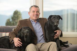 President and CEO Joel Yuhas sits with his two black labs