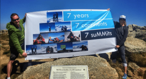 Kim Hess and her brother, Steven Hess, are shown holding up a celebratory banner for the completion of the Seven Summits.