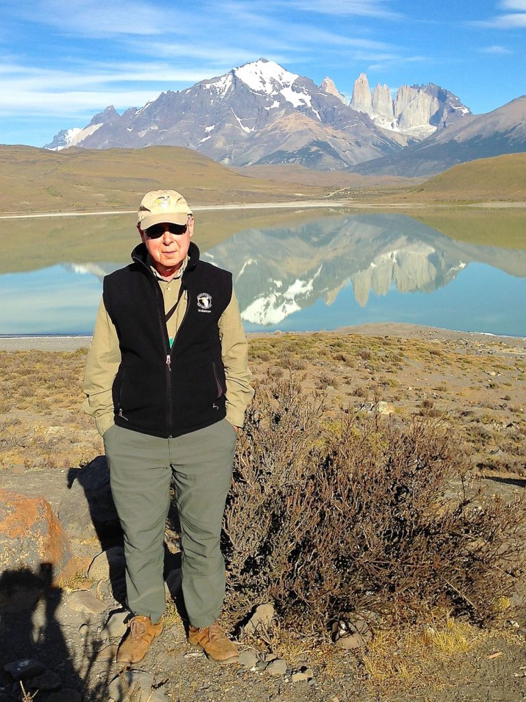 In this photo, Mike Bloom stands in front of a lake in Patagonia where he and his wife, Mike, went to go birding in 2015.