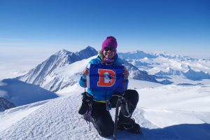 Kim Hess shows a Denver Broncos flag with Mount Vinson in Antarctica in the background.