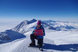 "Kim Hess holds a sign that says ""UCHealth"" as she kneels in the snow with Mount Vinson in the background. Wild swings in temperatures were among the challenges of climbing 'Seven Summits.'"