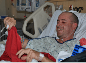 A patient in a hospital bed smiles after receiving a red T-shirt signed by his caregivers.