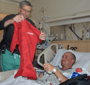 Dr. Daniel Huddle stands next to a patient's bedside and gives him a red T-shirt.