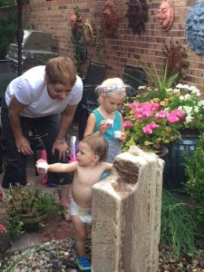 A grandmother out in a garden with her granddaughters. One is a baby in diapers. The other is about 4 years old and is looking at some pink flowers.