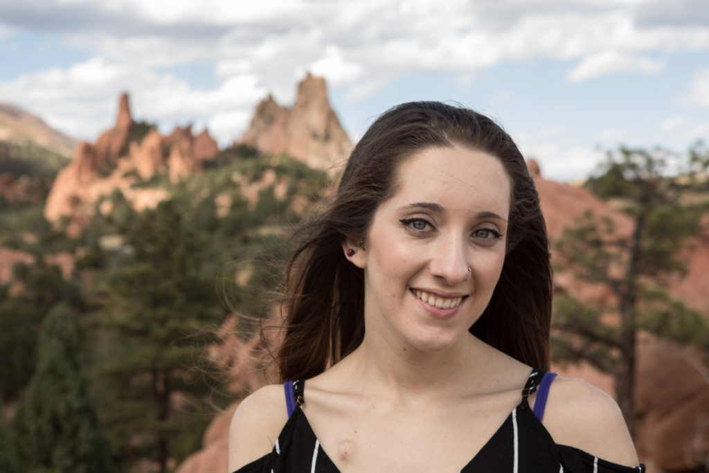 Hannah Moraski, 24, poses with red rocks behind her. She often has to have hospital treatments and gets to use virtual reality to travel virtually where she can't go in person.