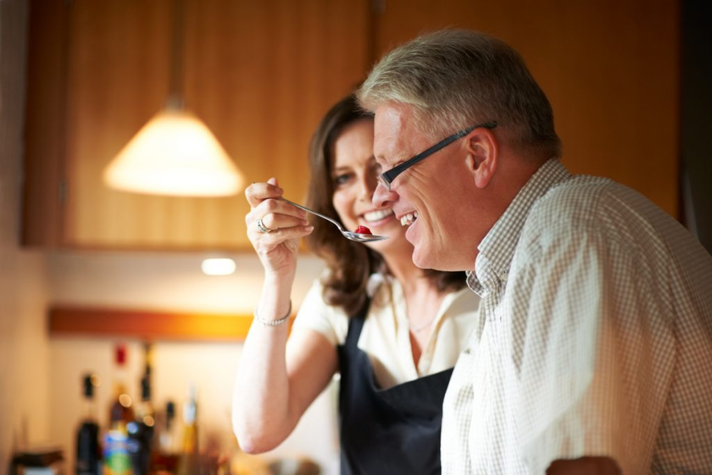 Photo of a woman giving a man a spoonful of some food.