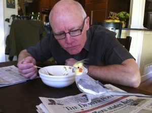 Patient Sonny Hutchison sits at his kitchen table, eating, while his pet bird sits on the table nearby.