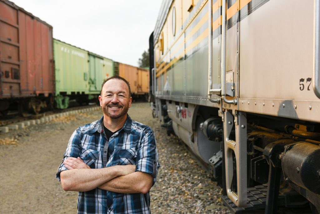 Stephen Mullen poses with some colorful train cars at the Colorado Railroad Museum. He was diagnosed with a brain tumor that threatened his hearing.