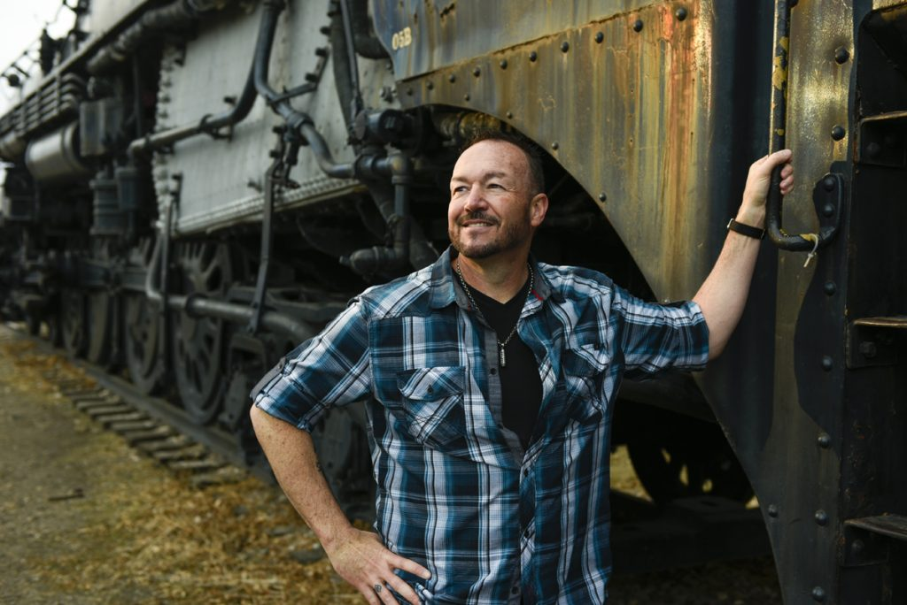 Stephen Mullen poses with a train at the Colorado Railroad Museum. Train engineer back aboard after brain tumor threatens hearing.