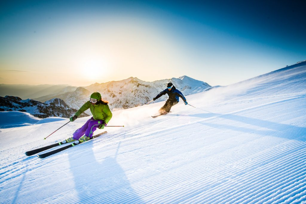 Two skiers ski down a snowy slope with sun in the background.