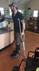 Jordan Leigh walks in two boots with crutches on the first day out of his wheelchair after rupturing two Achilles tendons.