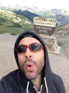 Actor Jordan Leigh in a selfie at the top of Loveland Pass in Colorado with a sign behind him that says Loveland Pass, Elevation, 11,990, Continental Divide.