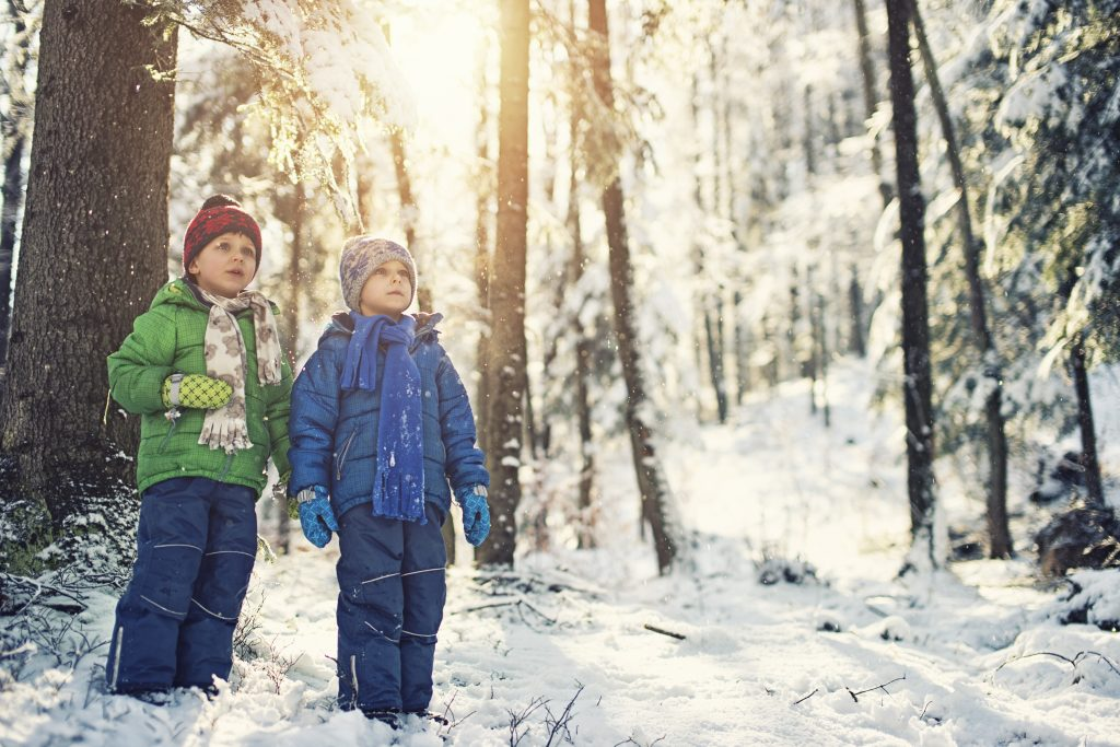 Two children wear winter parkas and hats as they stand in a snowy forest.