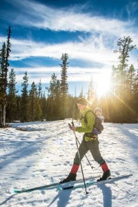 mom cross country skis with baby on her back