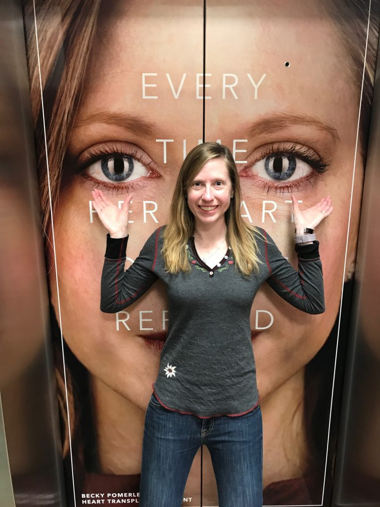 Becky Pomerleau poses with an ad that shows her face