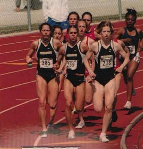 Becky was a competitive runner in high school and college. Here she runs with a group of runners on a field. She's in the lead.