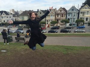Becky jumping and smiling in a park.