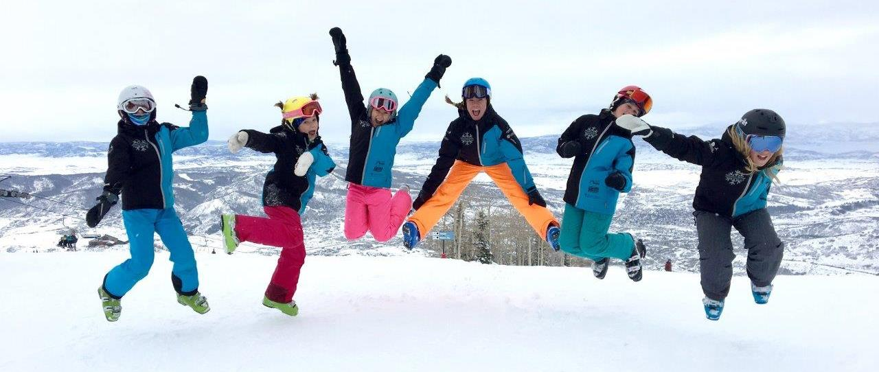 Members of the kids club jumping into the air for a photo shoot on the slopes.